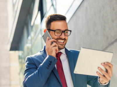 Handsome young smiling businessman having phone call